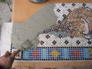 Fliesenkleber wird auf das Mosaik gespachtelt