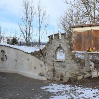 Raumgestaltung: Eine Ruinenwand mit Zinnen und gotischem Fenster